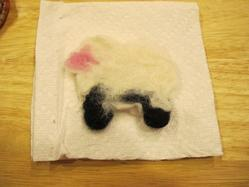 a cookie cutter sheep made with wool roving